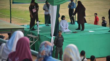 Seorang wanita dicambuk setelah ketahuan melakukan hubungan seks pranikah di sebuah stadion di Lhokseumawe di provinsi Aceh (31/7/2019). Dua pria dan seorang wanita dicambuk secara terbuka sebanyak 100 kali karena melanggar hukum Islam di daerah tersebut. (AFP Photo/Rahmad Mirza)