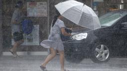Seorang wanita Taiwan mengenakan payung berjalan melawan hembusan angin kencang yang ditimbulkan oleh topan Lekima di Taipei, Taiwan, Jumat (9/8/2019). Topan Lekima saat ini tengah menghantam Taiwan, membawa angin ribut dengan kecepatan 190 km/jam. (AP Photo / Chiang Ying-ying)
