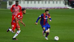 Pemain Barcelona Lionel Messi (kanan) menggiring bola melewati pemain Granada Yangel Herrera pada pertandingan La Liga di Stadion Camp Nou, Barcelona, Spanyol, Kamis (29/4/2021). Barcelona kalah 1-2. (AP Photo/Joan Monfort)