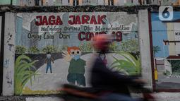 Pengendara motor melintasi mural bertuliskan protokol kesehatan COVID-19 di Kawasan Kota Bambu, Jakarta, Selasa (20/10/2020). Satgas Penanganan Covid-19 mencatat sampai  Rabu, 21 Oktober 2020, pukul 12.00 WIB warga yang terkonfirmasi positif Covid-19 bertambah 4.267 kasus. (Liputan6.com/Johan Tallo)