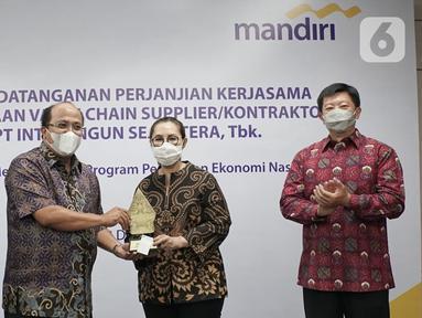 Direktur Commercial Banking Bank Mandiri Riduan (kedua kiri) memberikan cinderamata kepada Komisaris Utama Inti Bangun Sejahtera Farida Bau pada acara perjanjian kerjasama pembiayaan rekanan sebesar Rp250 miliar pada tahap awal di Jakarta, Selasa (22/12/2020). (Liputan6.com/HO/Wedi)