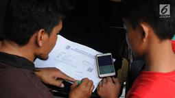 Orang tua wali murid menulis tanda bukti pendaftaran PPDB di posko SMP 11 di Rawa Buntu, Serpong, Tangsel, Jumat (13/07). Mereka protes karena tidak bisa mengetahui kelanjutan hasil pendaftaran putra-putrinya lewat situs PPDB. (Merdeka.com/Arie Basuki)