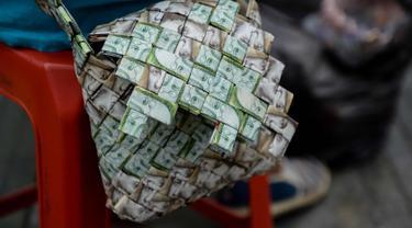 Tampilan tas dari lembaran Bolivar buatan Rojas di Caracas, Venezuela, pada 30 Januari 2018. Inflasi yang tinggi membuat mata uang tersebut terus kehilangan nilainya. (AFP Photo/Federico Parra)