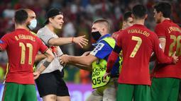 Petugas keamanan stadion menahan seorang penyusup lapangan setelah pertandingan sepak bola Grup F UEFA EURO 2020 antara Portugal melawan Prancis yang berlangsung di Puskas Arena, Budapest pada 23 Juni 2021. (AFP/Pool/Franck Fife)
