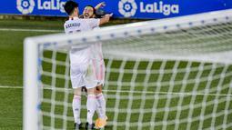 Gelandang Real Madrid, Eden Hazard berselebrasi dengan rekannya Marco Asensio usai mencetak gol ke gawang Deportivo Alaves pada pertandingan lanjutan La Liga Spanyol di stadion Mendizorroza di Vitoria, Minggu (24/1/2021). Madrid menang besar atas Alaves 4-1. (AP Photo/ Alvaro Barrientos)