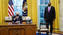 Menteri Pertahanan Lloyd Austin mendengarkan Presiden AS Joe Biden berbicara sebelum menandatangani Perintah Eksekutif yang membatalkan larangan bagi transgender untuk masuk militer AS pada era Donald Trump di Kantor Oval Gedung Putih, Washington, Senin (25/1/2021). (AP Photo/Evan Vucci)