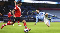 Gelandang Manchester City, Bernardo Silva, berusaha menghadang pemain Southampton, Ryan Bertrand, pada laga Liga Inggris di Stadion Etihad, Kamis (11/3/2021). City menang dengan skor 5-2. (Clive Brunskill/Pool via AP)