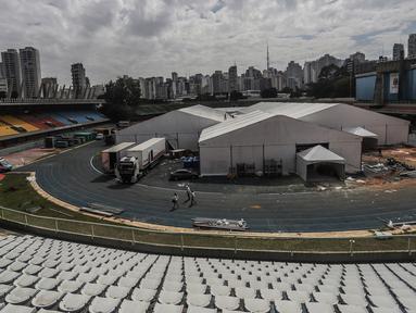 Orang-orang bekerja di lokasi pembangunan rumah sakit sementara di kompleks olahraga Ibirapuera di tengah merebaknya COVID-19 di Sao Paulo (16/4/2020). Jumlah kasus terkonfirmasi COVID-19 di Brasil melonjak dari 28.320 menjadi 30.425, kata Kemenkes Brasil pada Kamis (16/4). (Xinhua/Rahel Patrasso)