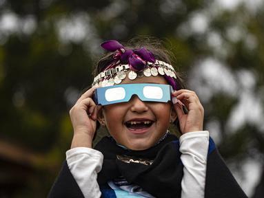 Magdalena Nahuelpan, seorang gadis Adat Mapuche, melihat gerhana matahari total menggunakan kacamata khusus di Carahue, La Araucania, Chile, Senin (14/12/2020). Gerhana matahari total terlihat dari Chile dan wilayah Patagonia utara Argentina. (AP Photo/Esteban Felix)