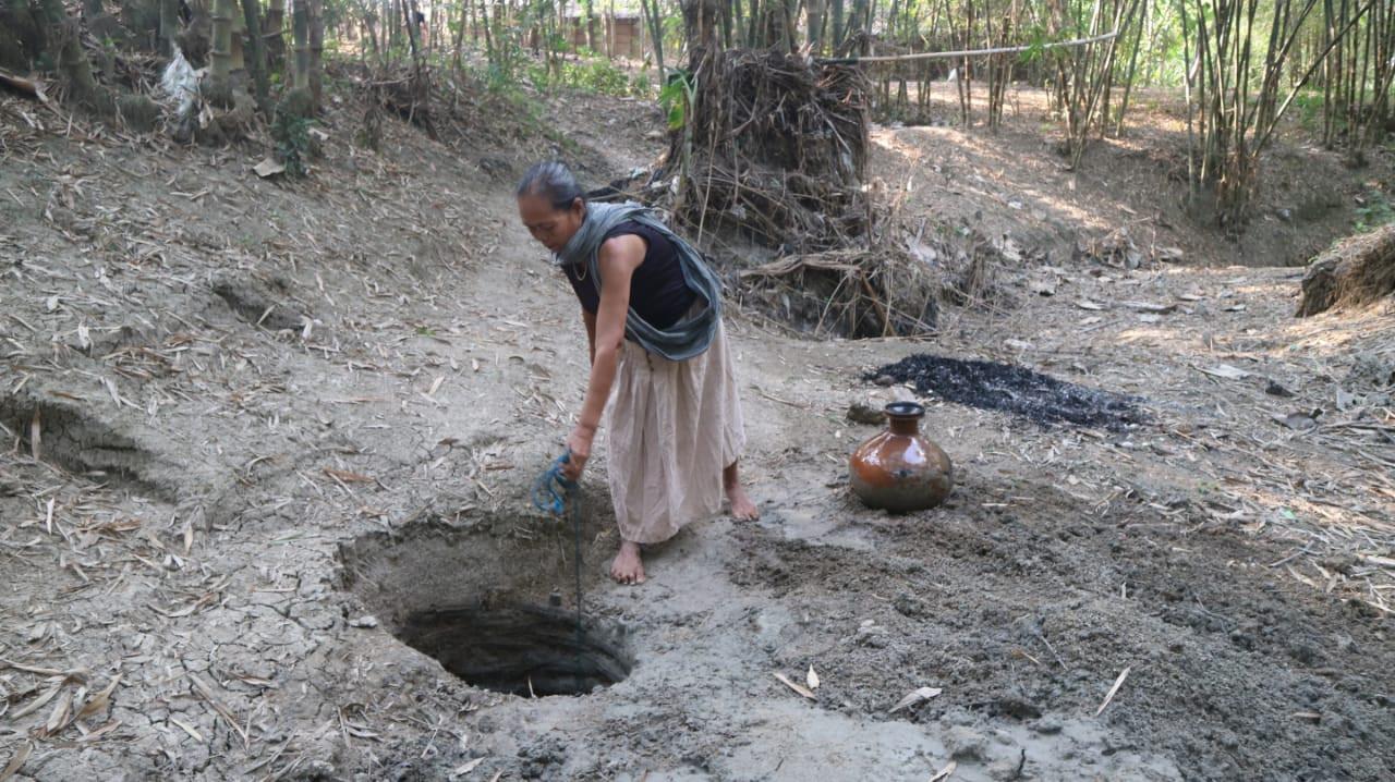 Seorang warga yang sudah tua membuat lubang di dasar sungai kering di desa Ngrandah, Kabupaten Grobogan untuk mencari sumber air. (foto: Liputan6.com / Felek Wahyu)