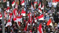 Peserta aksi massa Gerakan Nasional Kedaulatan Rakyat mengibarkan bendera Merah Putih saat melakukan unjuk rasa di depan Gedung Bawaslu, Jakarta, Selasa (21/5/2019). Mereka menolak hasil Pemilu 2019 yang dinilai banyak terdaopat kecurangan. (Liputan6.com/Helmi Fithriansyah)