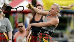 Dee Dee Arbutina melempar beban saat mengikuti Grandfather Mountain Highland Games ke-64 di MacRae Meadows, Linville, North Carolina, AS, Jumat (12/7/2019). Kejuaraan ini digelar untuk merayakan sejarah dan budaya Skotlandia. (AP Photo/Chuck Burton)