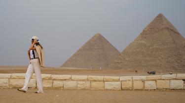 Ibu Negara AS Melania Trump memegang topinya saat berkunjung ke situs bersejarah Piramida Giza, Kairo, Mesir (6/10). Melania tampil mengenakan busana safari klasik saat mengunjungi destinasi terakhir selama seminggu di Afrika. (AP Photo/Carolyn Kaster)