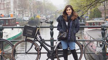 Gaya Nisya Ahmad saat berlibur di Amsterdam, Belanda pun tetap terlihat stylish. Ia memilih menggunakan jaket berwarna hitam yang dipadukan dengan syal serta tas dan sepatu berwarna senada. (Liputan6.com/IG/@nissyaa)