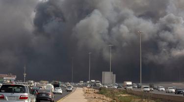 Mobil-mobil melaju saat asap hitam  membumbung menyelimuti gedung Stasiun Kereta Api Cepat Haramain di kota Jeddah, Arab Saudi, Minggu (29/9/2019). Akibat kebakaran tersebut, setidaknya sepuluh orang terluka. (Photo by - / AFP)