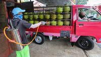 Karyawan menyemprotkan cairan disinfektan ke tabung gas ukuran 3 kg di Agen LPG 3 kg, Bojongsari, Depok, Senin (4/5/2020). Selain penyemprotan, sejumlah karyawan agen juga dibekali dengan masker dan sarung tangan untuk menghindari penyebaran Covid-19. (Liputan6.com/Fery Pradolo)