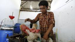 Hamidi saat mengolah sampah plastik menjadi bahan bakar di bengkel kerjanya dekat TPA Rawa Kucing, Tangerang, (17/3). Bahan bakarnya tersebut juga dapat untuk menjadi bahan bakar kendaraan. (REUTERS / Beawiharta)