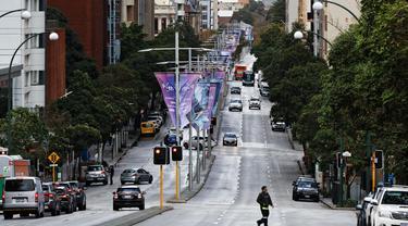 Seorang pria melintasi Saint Georges Terrace, jalan raya utama kota di Perth (29/6/2021). Beberapa kasus positif virus corona Covid-19 telah menyebabkan empat hari penguncian wilayah metropolitan Perth. (AFP/Trevor Collens)