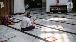 Umat Muslim membaca Al-Quran di Masjid Cut Meutia, Jakarta, Kamis (30/7/2020). Masjid Cut Meutia akan menggelar Salat Idul Adha esok hari dengan menerapkan protokol kesehatan pencegahan Covid-19. (Liputan6.com/Faizal Fanani)