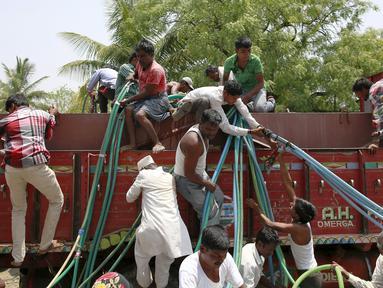Warga mengambil air dari truk tangki bantuan dari pemerintahannya di Desa Masurdi, Latur, India (17/4). Sejumlah wilayah di India mengalami kesulitan air bersih karena kekeringan akibat kemarau panjang melanda negerinya. (REUTERS/Danish Siddiqui)