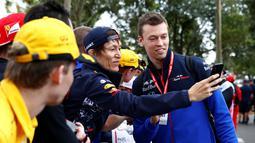 Pembalap F1 Toro Rosso, Daniil Kvyat berselfie bersama penggemarnya saat tiba di Sirkuit Melbourne Grand Prix di Melbourne, Jumat (15/3). (Reuters/Edgar Su)
