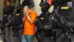 WNA pelaku pemalsuan dan pencurian data elektronik (skimming) saat di Polda Metro Jaya, Jakarta, Senin (19/3). Polisi menyita barang bukti 196 kartu ATM, dua alat deep skimmer, laptop, paspor, dan uang tunai Rp 50 juta. (Liputan6.com/Arya Manggala)