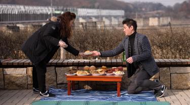 "Pengungsi Korea Utara, Kim Jung-ae (kiri) mengatur meja untuk memberikan penghormatan kepada kerabat dan leluhur pada Tahun Baru Imlek di ""desa harapan"" Imjingak, dekat zona demiliterisasi yang memisahkan kedua Korea di Paju, Selasa (5/2). (Ed JONES/AFP)"