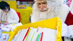 Seorang pria berpakaian Santa Claus membawa surat - surat dari anak - anak di desa Himmelpfort, Jerman, (10/11/2015). Kegiatan  ini dalam rangka menyambut hari Natal. (REUTERS/Hannibal Hanschke)