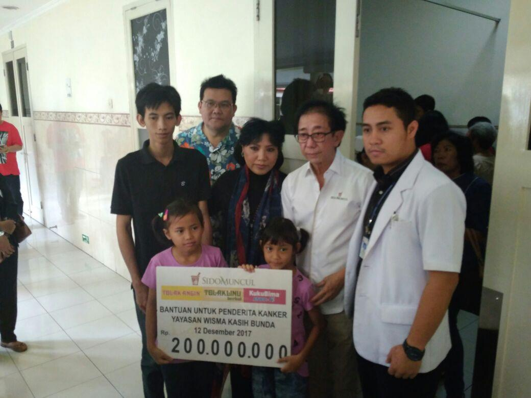 Direktur PT Sido Muncul Tbk, Irwan Hidayat menyerahkan bantuan pengobatan Rp 200 juta kepada Intan Guswanti, penderita kanker stadium akhir. (foto :Liputan6.com/edhie prayitno ige)