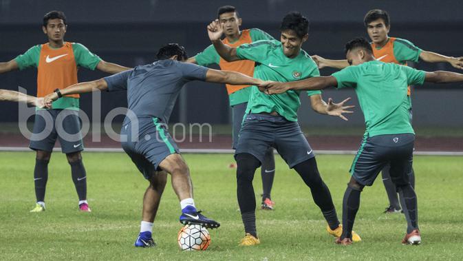 Pemain Timnas Indonesia, Hanif Sjahbandi, berebut bola dengan asissten pelatih, Bima Sakti saat latihan. Uji coba ini menjadi laga terakhir Timnas U-22 sebelum berangkat untuk pelatihan panjang di Spanyol. (Bola.com/Vitalis Yogi Trisna)