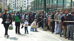 Warga antre untuk tes COVID-19 di dekat daerah perumahan di Qingdao, China, Senin (12/10/2020). Kota Qingdao melakukan tes COVID-19 untuk seluruh populasi lebih dari 9 juta orang setelah kasus baru muncul terkait dengan rumah sakit yang merawat pasien terinfeksi dari luar negeri. (Chinatopix via AP)