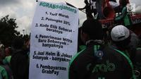 Sebuah poster yang berisi tuntutan pengemudi ojek online dibentangkan saat aksi di seberang Istana Merdeka, Jakarta, Selasa (27/3). Mereka juga meminta legalitas angkutan ojek online. (Liputan6.com/Arya Manggala)