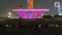 Suasana saat warga menyaksikan pertunjukan video mapping di Monumen Nasional (Monas), Jakarta, Minggu (22/12/2019). Acara ini berlangsung di pelataran barat Tugu Monas pada 22-31 Desember 2019. (Liputan6.com/Herman Zakharia)