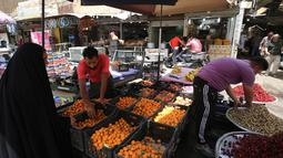 Pedagang buah melayani pembeli selama bulan suci Ramadan di pasar Baghdad (24/5/2019). Baghdad adalah salah satu kota terbesar di dunia dan menjadi rumah bagi umat Muslim, Kristiani, Yahudi dan penganut paganisme dari seluruh Timur Tengah dan Asia Tengah. (AFP Photo/Ahmad Al-Rubaye)