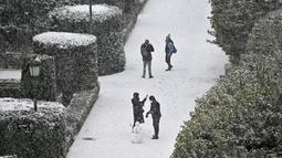 Orang-orang membuat manusia salju di Taman Sabatini di luar Istana Kerajaan, Madrid, Spanyol, Jumat (8/1/2021). Badai Filomena mengakibatkan salju lebat turun di Madrid dan seluruh Spanyol. (GABRIEL BOUYS/AFP)