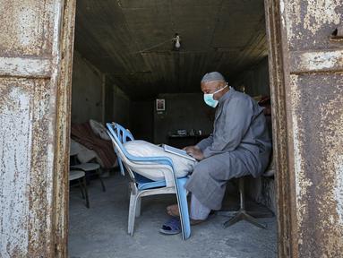 Seorang tukang roti membaca Al-Quran selama bulan suci Ramadan di Kota Gaza, Palestina, Jumat (1/5/2020). (MOHAMMED ABED/AFP)