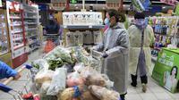 Seorang wanita mengenakan jas hujan dan masker membeli makanan di sebuah supermarket di Wuhan di provinsi Hubei, China tengah, Senin, (10/2/2020). China melaporkan kenaikan angka kematian akibat wabah virus corona. (Chinatopix via AP)