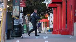 Polisi melintas di lokasi penikaman yang menewaskan dua orang di Chinatwown, Los Angeles, AS (26/1). Diketahui korban dan pelaku sebelumnya telah memiliki perselelisihan. (AP Photo / Reed Saxon)