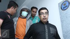 Penyanyi Iwa K dikawal petugas seusai menjalani proses assessment di Balai Laboratorium Narkoba BNN, Jakarta, Selasa (2/5). Proses assessment dilakukan untuk melihat sejauh apa tingkat ketergantungan Iwa K terhadap narkoba. (Liputan6.com/Herman Zakharia)