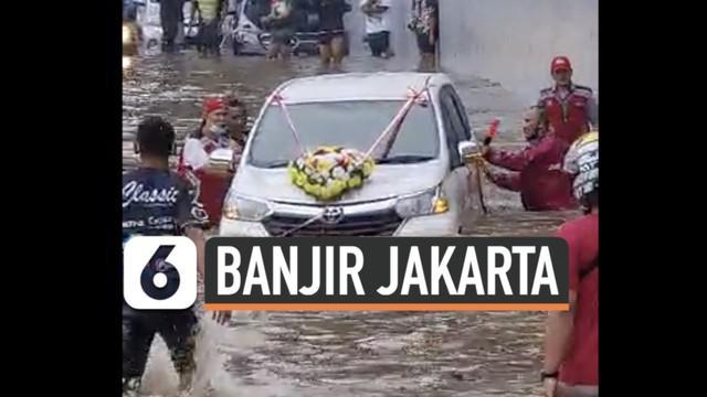 Banyak kendaraan mobil terjebak di ruas jalan tol JORR yang masih terendam banjir Sabtu (20/2) siang. Salah satunya mobil pengantin yang terpaksa didorong untuk keluar dari banjir.