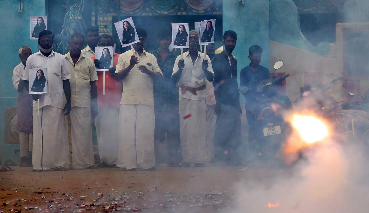 Warga desa menyalakan petasan sambil memegang plakat bergambar Wakil Presiden AS terpilih Kamala Harris menjelang pelantikan Harris di Thulasendrapuram, selatan Chennai, Tamil Nadu, India, Rabu (20/1/2021). Thulasendrapuram adalah kampung halaman kakek Harris dari pihak ibu. (AP Photo/Aijaz Rahi)