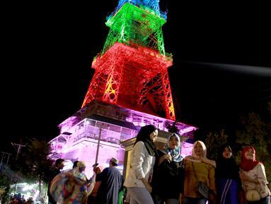 Warga berfoto dekat Pakaya Tower di kawasan taman Limboto, Kabupaten Gorontalo, Sabtu (12/1). Pakaya Tower berdiri megah bak Menara Eiffel dengan tata lampu warna-warni. (Liputan6.com/Arfandi Ibrahim)