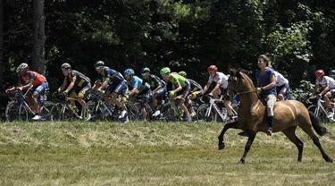 Seorang pengendara kuda mengiringi pebalap Tour de France pada etape ke-16 dengan jarak 165 km dari Le Puy-en-Velay dan Romans-sur-Isere, (18/7/2017).  (AFP/Lionel Bonaventure)