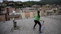 Vittoria Oliveri (depan) bermain tenis dengan Carola di atas atap rumah mereka selama lockdown COVID-19 di Finale Ligure, Wilayah Liguria, Italia (19/4/2020). Setiap hari Carola, 11, dan Vittoria, 13, bermain tenis dari satu atap ke atap lain di rumah mereka untuk berlatih. (AFP/Marco Bertorello)