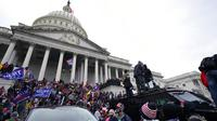 Massa pendukung Presiden Amerika Serikat Donald Trump berdiri di atas kendaraan polisi di Capitol Hill, Washington, Amerika Serikat, Rabu (6/1/2021). Kericuhan terjadi saat massa pendukung Donald Trump merangsek masuk ke dalam Gedung Capitol Hill. (AP Photo/Julio Cortez)