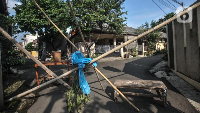 Sebuah bambu saat menutup akses permukiman warga RT 003 RW 003, Kelurahan Cilangkap, Kecamatan Cipayung, Jakarta, Selasa (25/5/2021). Sebagian besar warga yang positif Covid-19 telah dibawa ke RS Darurat Wisma Atlet dan sisanya menjalani isolasi mandiri (merdeka.com/Iqbal S Nugroho)