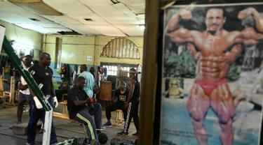 Sejumlah binaragawan mengangkat beban saat berolahraga di gym Kaloleni, di Nairobi, Kenya (9/1). (AFP Photo/Simon Maina)