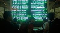 Calon penumpang melihat papan informasi penundaan penerbangan di Bandara Ngurah Rai, Bali, Kamis (28/6). Pihak pengelola menutup sementara aktivitas bandara maupun penerbangan karena gangguan abu vulkanis erupsi Gunung Agung. (AP/Firdia Lisnawati)