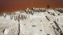 Pemandangan arial ini menunjukkan deretan perahu yang digunakan untuk memanen garam di Danau Retba (Danau Merah Muda) di Senegal pada 16 Maret 2021. Kandungan garam Danau Reba sangat tinggi, yakni 40 persen, bersaing dengan Laut Mati, bahkan bisa melampauinya ketika musim kering. (MARCO LONGARI/AFP)