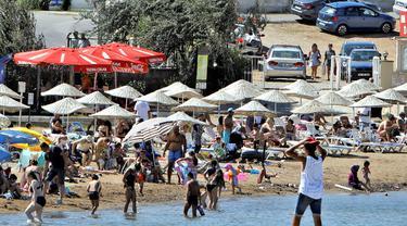 Warga berlibur di sebuah pantai di Distrik Ayvalik, Provinsi Balikesir, Turki, 4 Agustus 2020. Ramainya kunjungan warga Turki ke pantai-pantai selama liburan empat hari Idul Adha pekan lalu memicu kekhawatiran merebaknya kembali pandemi COVID-19 di negara itu. (Xinhua/Osman Orsal)